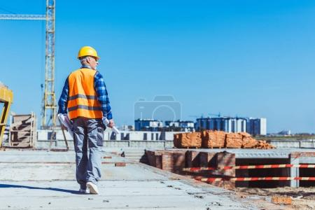 Photo for Builder in reflective vest and hardhat walking across a construction site with rolls of plans in his hands - Royalty Free Image