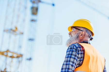 Photo for Builder in reflective vest and hardhat standing at construction site, looking up - Royalty Free Image