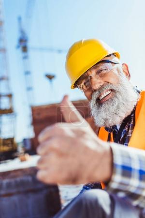 Photo for Smiling worker in reflective vest and hardhat sitting at construction site and showing thumb up - Royalty Free Image