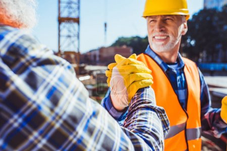 Foto de Sonriente trabajador de la construcción uniforme protector sacudariendo las manos con colega - Imagen libre de derechos