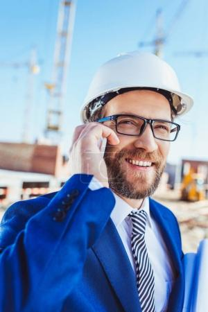 Businessman talking on phone at construction site