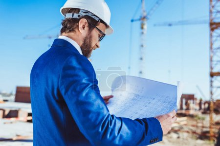 Businessman in hardhat reading building plans