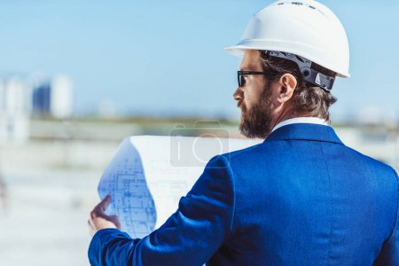Photo for Businessman in hardhat and suit examining building plans - Royalty Free Image