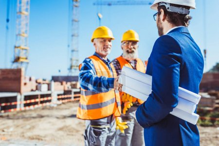 Construction worker and businessman shaking hands