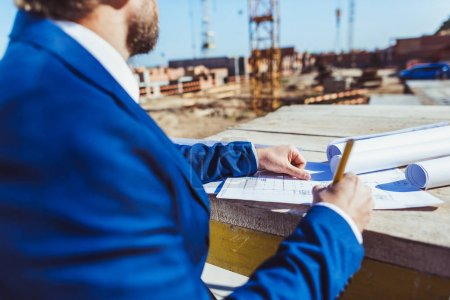 Businessman taking notes at construction site