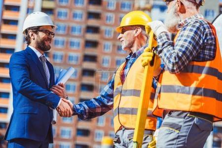 Photo for Cropped shot of construction worker in reflective vest shaking hands with businessman wearing hardhat - Royalty Free Image