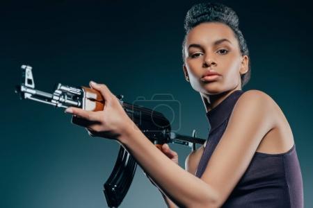 Photo pour Attrayant à la mode afro-américaine fille posant avec un fusil - image libre de droit