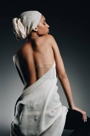 Photo for Back view of elegant sensual african american woman posing in white cloth and turban, on grey - Royalty Free Image