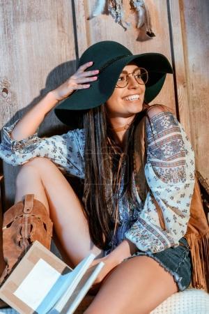 Photo pour Fille de Bohême chic, assis avec un livre sur un banc dans une maison en bois - image libre de droit