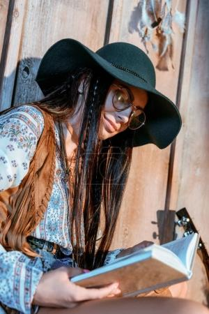 girl in boho style reading book