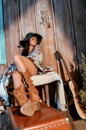 Photo for Beautiful bohemian woman sitting on a bench with legs on suitcase in wooden house - Royalty Free Image