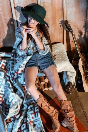 Photo pour Femme souriante de Bohême siégeant avec harmonica en mains - image libre de droit