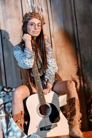 hippie girl posing with acoustic guitar
