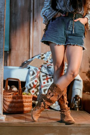 Photo for Cropped image of bohemian woman in brown shoes and jeans shorts in a wooden house - Royalty Free Image