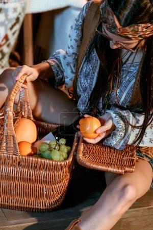 bohemian woman holding orange