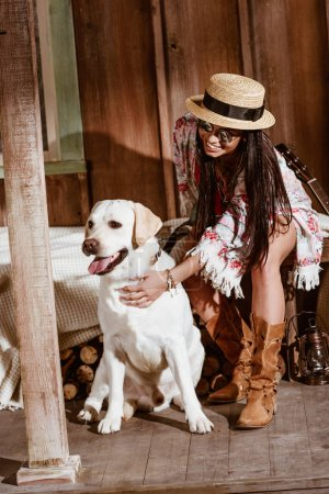 woman in boho style petting dog