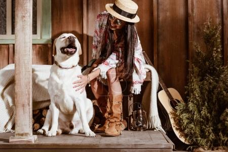woman in boho style petting dog