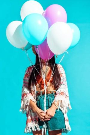 Hippie woman covering face with balloons