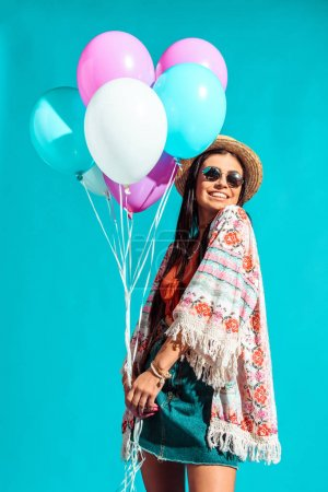 Photo for Happy Hippie girl holding colored helium balloons isolated on turquoise - Royalty Free Image