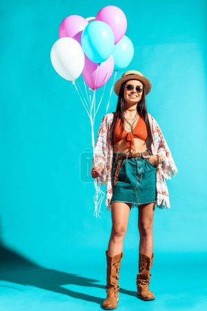 Bohemian woman holding colored balloons