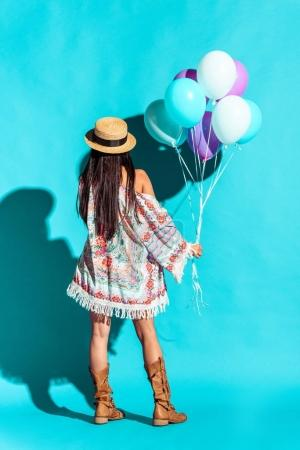 Hippie woman holding colored balloons