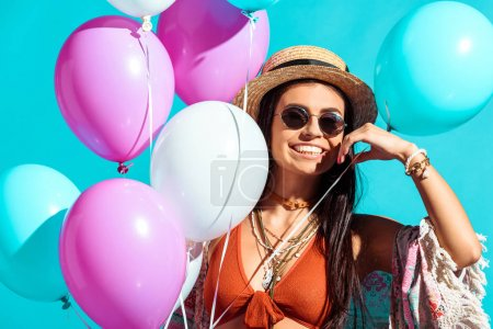 Photo for Happy bohemian girl standing with helium balloons isolated on turquoise - Royalty Free Image