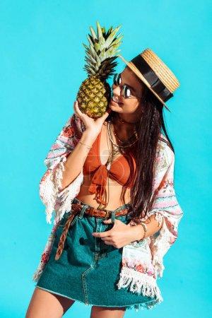 Hippie girl holding pineapple