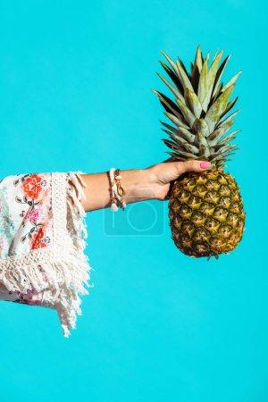Bohemian girl holding pineapple in hand