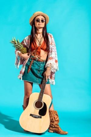 girl standing with pineapple and guitar