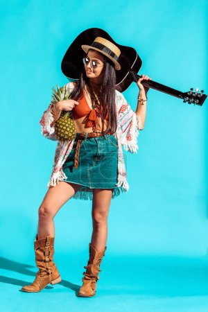 woman standing with pineapple and guitar