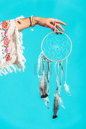 Hippie girl holding dreamcatcher in hand