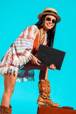 hippie tourist with black board and suitcase
