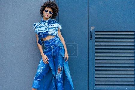 Photo pour Afro fille à la mode posant en denim vêtements et lunettes de soleil - image libre de droit