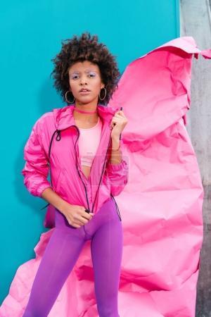 Photo pour À la mode modèle afro, posant dans les années 80 des vêtements de style sur turquoise avec papier rose - image libre de droit