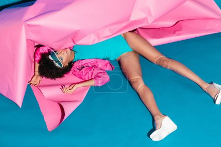 Photo for Beautiful african american model posing with pink paper for fashion shoot in 80s style - Royalty Free Image
