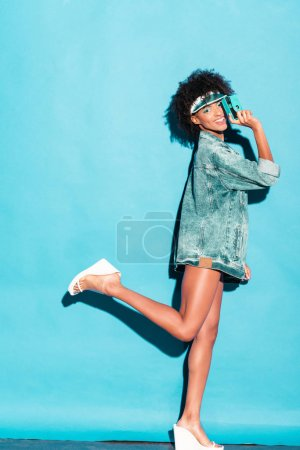 Photo for Attractive smiling afro model posing in jeans jacket with vintage photo camera, on turquoise - Royalty Free Image