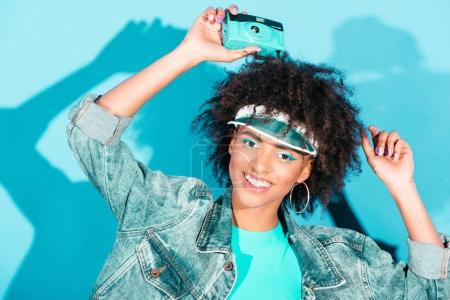 Photo for Beautiful afro model posing in jeans jacket with vintage photo camera, on turquoise - Royalty Free Image
