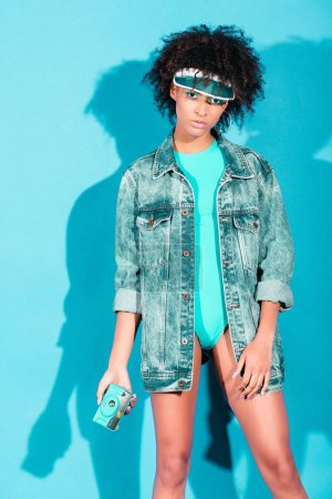 afro girl in jeans jacket with camera