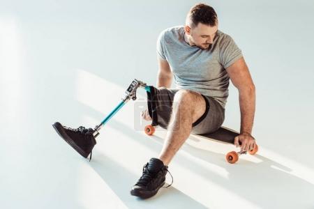 Photo pour Jeune homme avec prothèse de jambe assis sur planche à roulettes isolé sur blanc - image libre de droit
