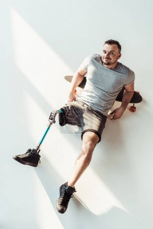 Photo for Overhead view of smiling man with leg prosthesis resting on skateboarding isolated on white - Royalty Free Image