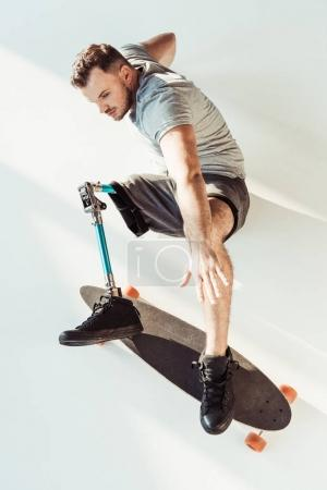 Photo for Overhead view of young man with leg prosthesis with skateboard isolated on white - Royalty Free Image