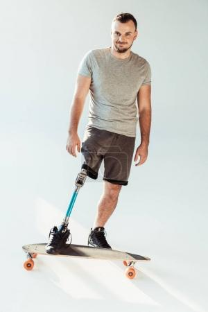 Photo for Smiling man with leg prosthesis standing on skateboard and looking at camera isolated on white - Royalty Free Image