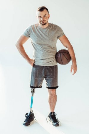 Photo for Paralympic basketball player with basketball ball sanding akimbo isolated on white - Royalty Free Image