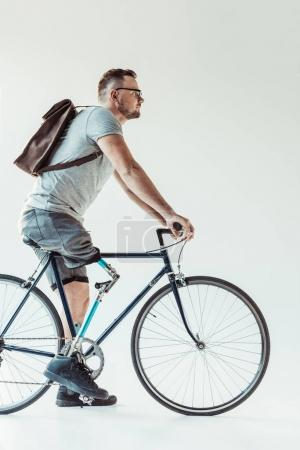 Photo for Side view of paralympic man with backpack on bicycle isolated on white - Royalty Free Image