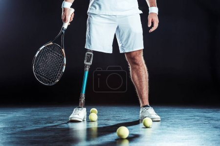 Photo for Cropped shot of  paralympic tennis player holding tennis racket with tennis balls on floor - Royalty Free Image