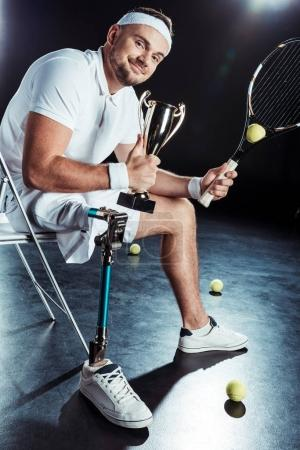 Photo for Happy paralympic tennis player with champion goblet resting on chair - Royalty Free Image