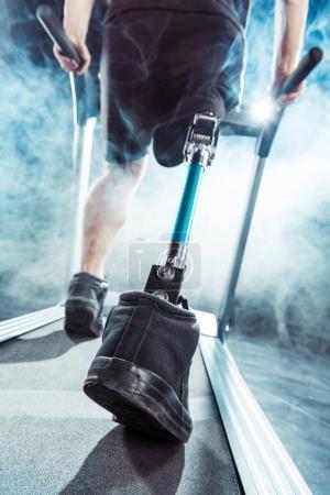 sportsman with leg prosthesis training on treadmill