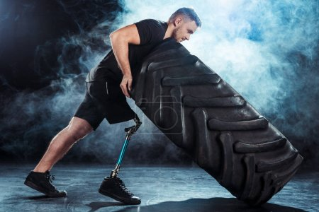 Photo for Side view of strong paralympic sportsman with leg prosthesis pulling tire - Royalty Free Image