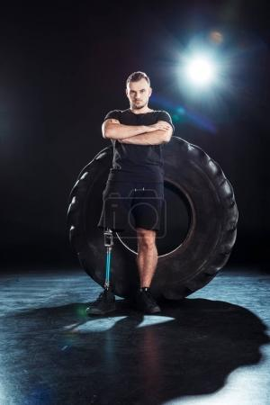 Paralympic sportsman leaning on tire