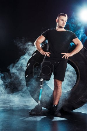 Photo for Young paralympic sportsman with leg prosthesis standing akimbo while leaning on tire - Royalty Free Image